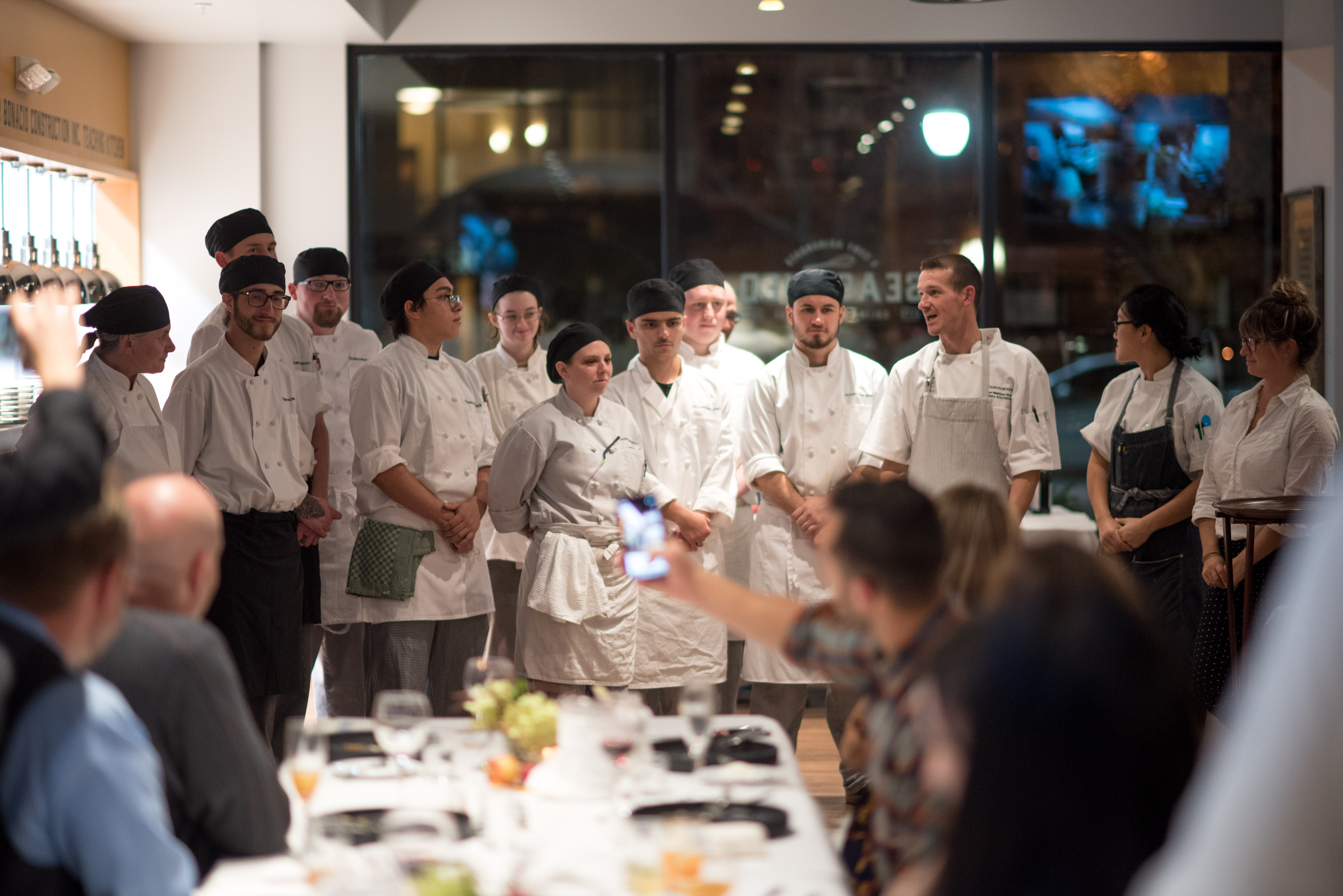 A group of culinary students stands in the dining room of Seasoned