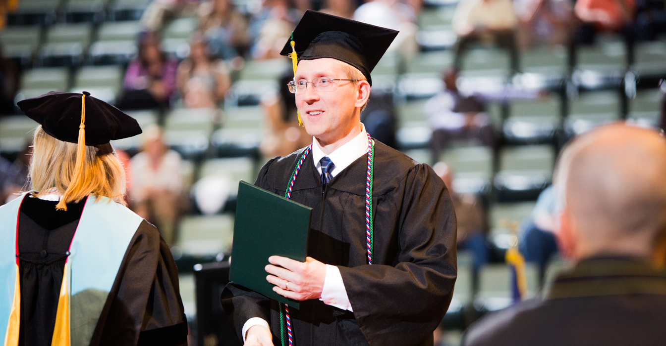 Adult male student accepting his diploma on stage at graduation