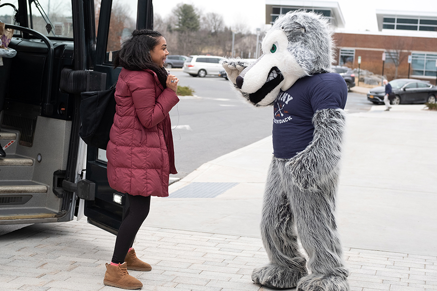 A prospective student from the New York City area interacts with Eddy Rondack during an April bus trip organized by SUNY Adirondack's Admissions Office.