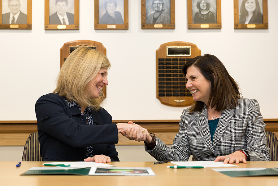 SUNY Adirondack President Kristine Duffy, left, and Castleton University President Karen M. Scolforo sign an agreement to create a pathway for degree completion between both colleges.