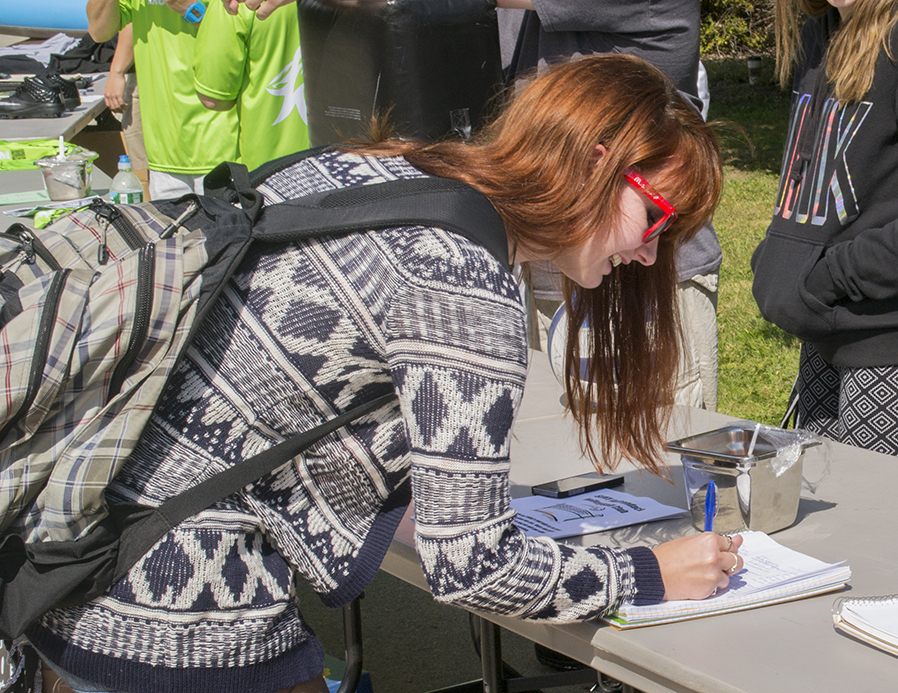 A student signs up for a club during a past Club Drive.