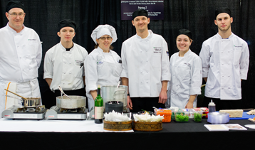 Culinary students and instructors behind table of ingredients and cookware
