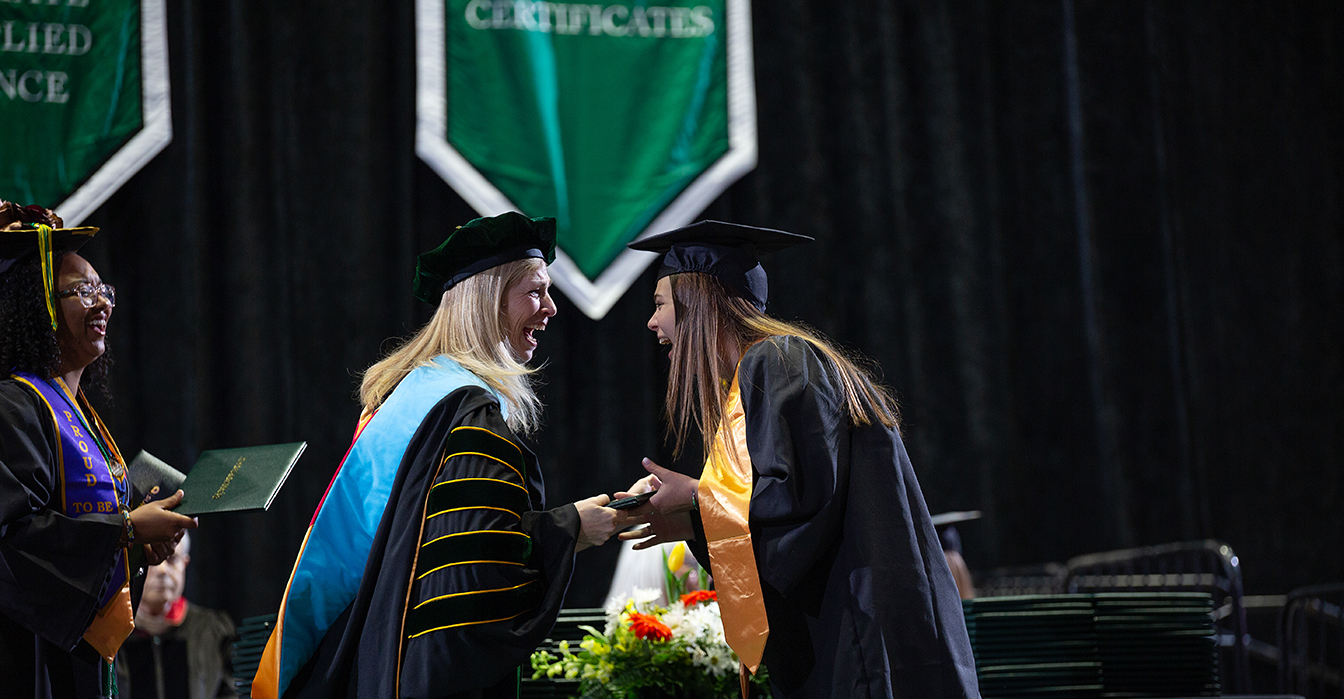 SUNY Adirondack President Dr. Kristine Duffy hands a graduate a diploma