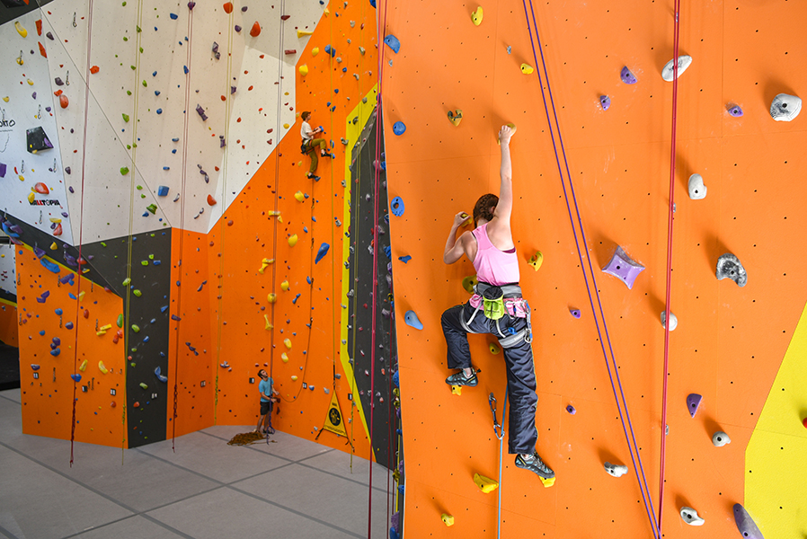 A young woman climbs a rock wall at Rocksport, an indoor climbing facility.