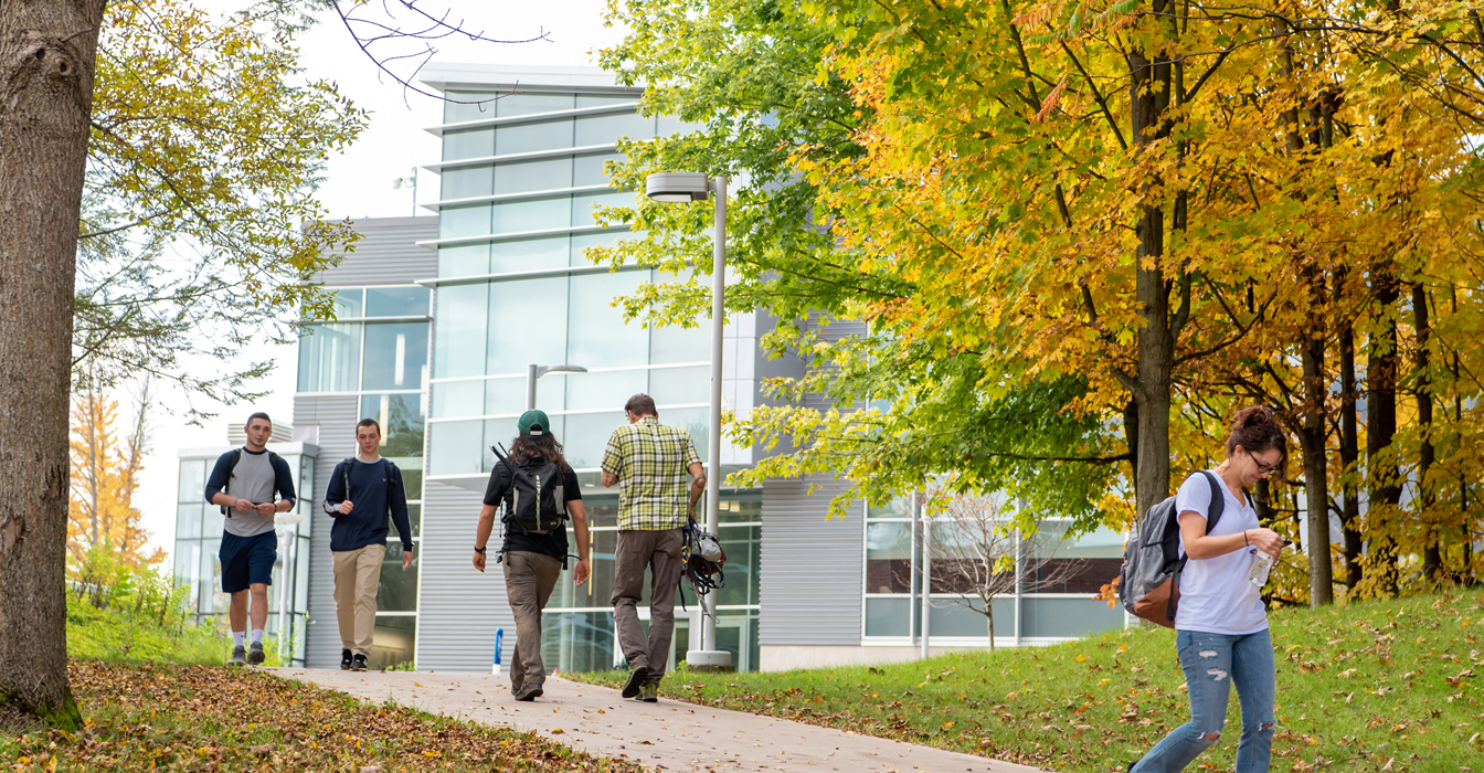 Male and female students walking on campus in the fall