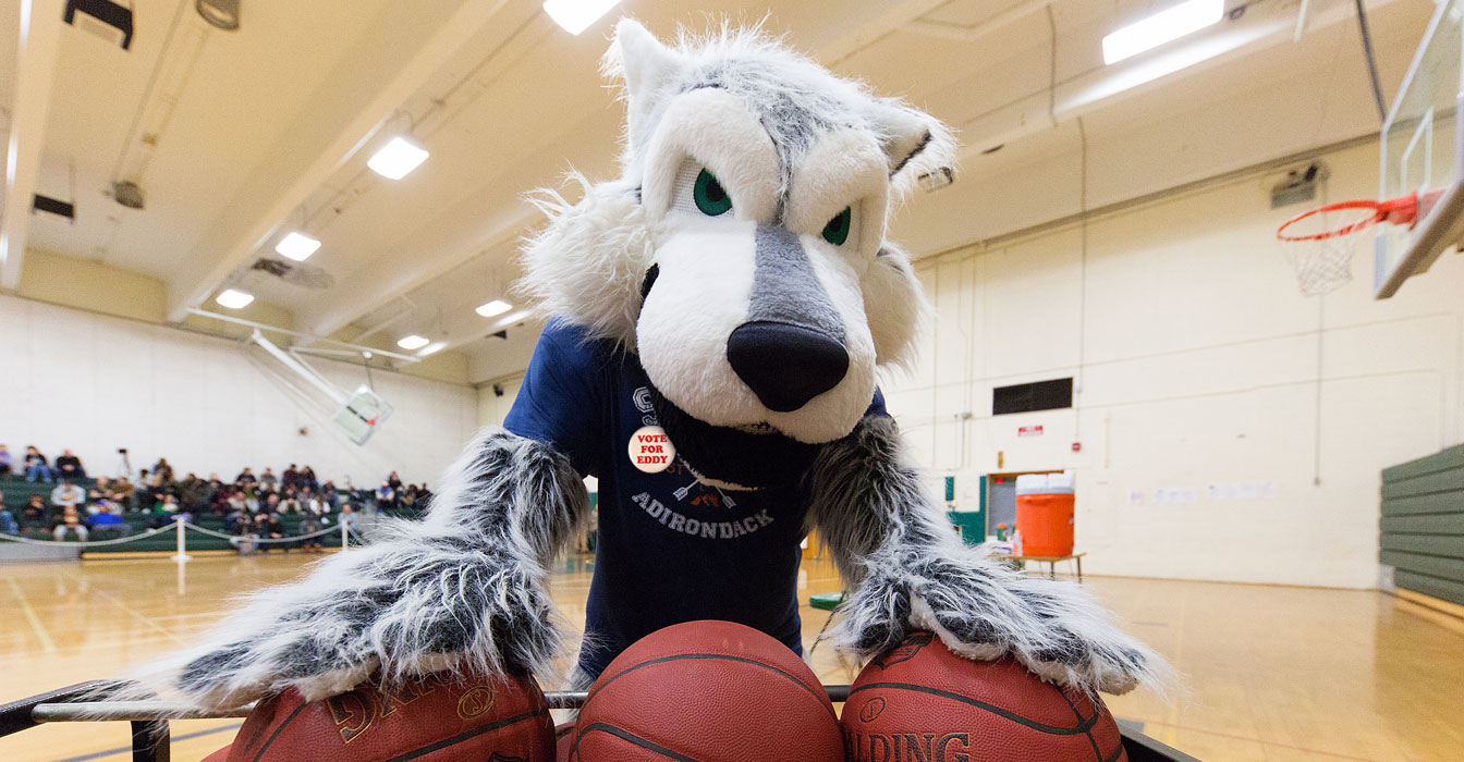 Mascot Eddy in the gym with basketballs