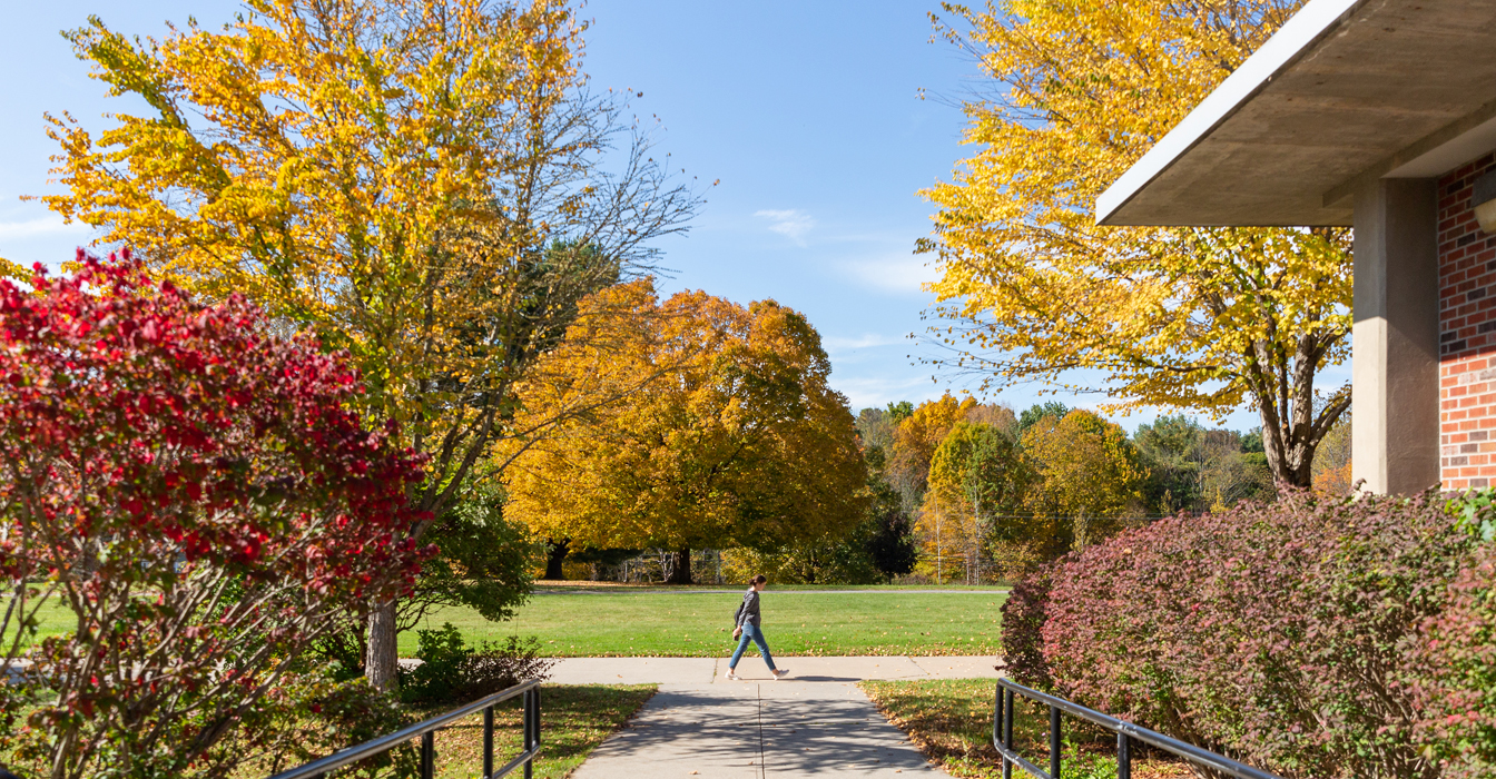 A female student walking on campus in the fall by the upper level of Washington Hall