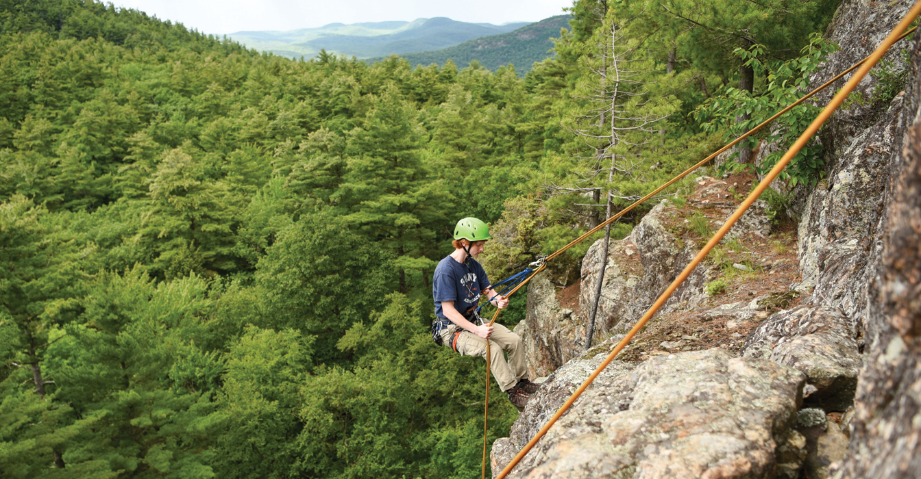 Male student rock climbing with a view of Lake George in the background