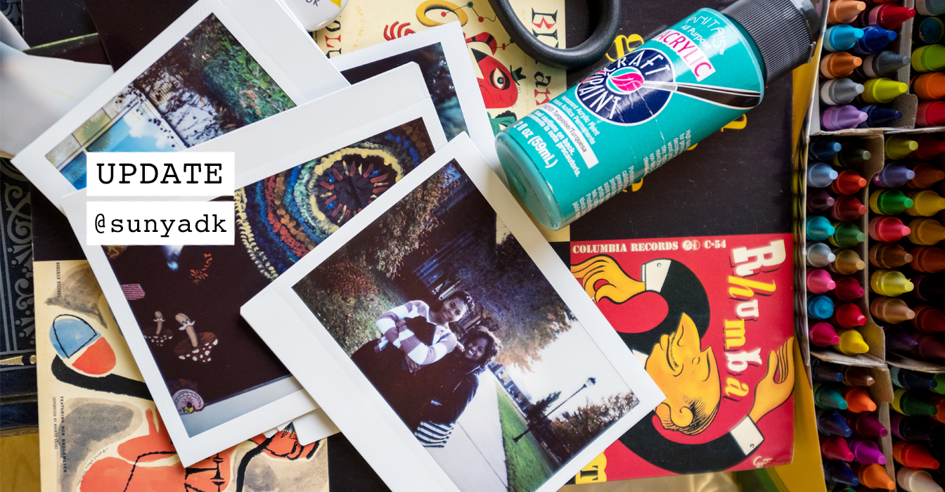 Image of art supplies on a desk with polaroid pictures of students on campus