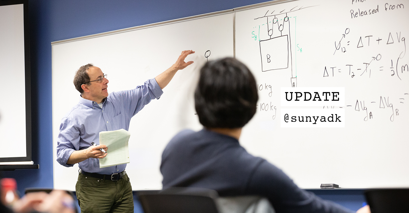 Male professor talking and writing on a white board in a classroom