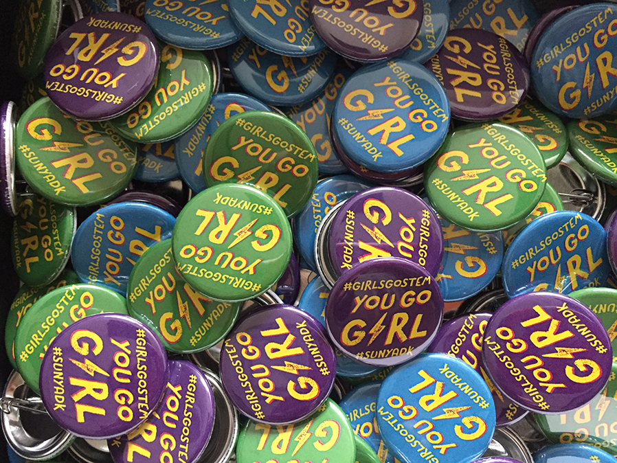 A box of buttons advertise the Girls Go Stem event.