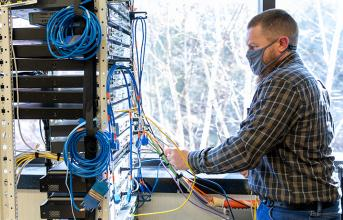 image of male cybersecurity student working in the networking lab