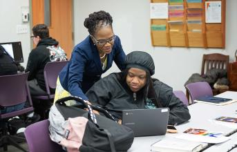Professor Hayles assists student at computer