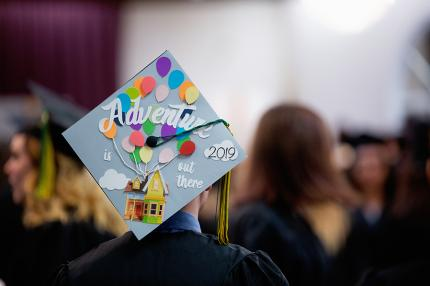 Student wears graduation cap reading 'Adventure is out there: 2019.'