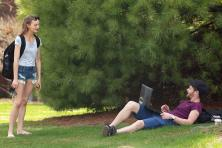 Students interacting outside on laptops in the summer