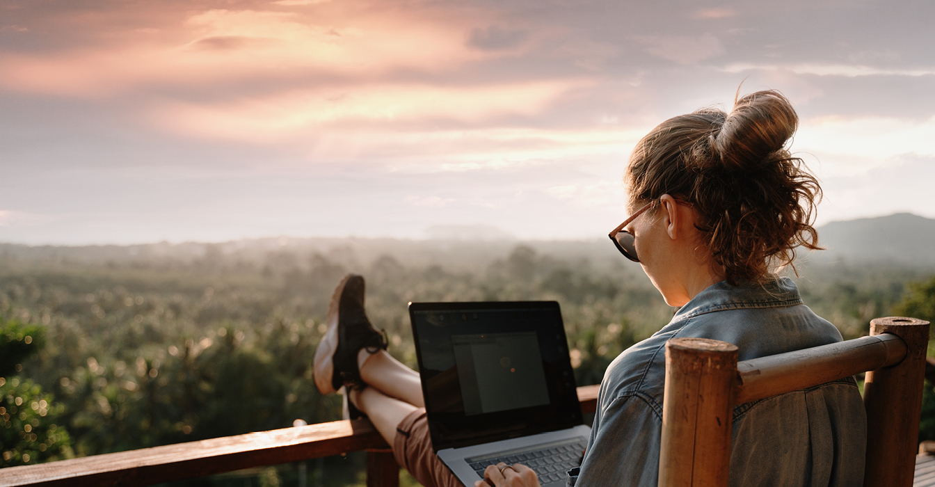 woman sitting on deck outside working remotely on a laptop
